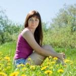 dziewczyna siedzi w mniszek łąka — Zdjęcie stockowe