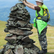 Stock Photo: Alpinist wommaking stone pile
