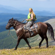 Female tourist  on horseback — Stock Photo