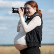 Royalty-Free Stock Photo: Pregnant woman  with photocamera