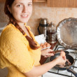 Young woman adds eggs to hot skillet — Stock Photo #6854620