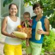 Women and baby with harvested vegetables — Stock Photo