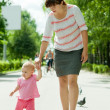 Mother with toddler walking on road — Stock Photo #6854812