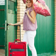 Woman with luggage near home — Stock Photo #6854891