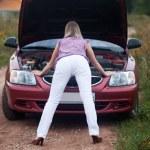 Sexy girl looking under car hood — Stock Photo