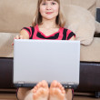 Girl sitting on floor and using laptop — Stock Photo
