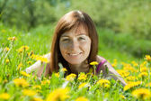 Freckle woman relaxing in dandelion — Stock Photo