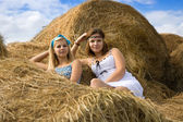 Country girls laying on hay — Stock Photo