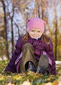 Girl sitting in autumn park — Stock Photo