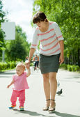 Mother with toddler walking on road — Stock Photo