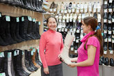 Women chooses high shoes at shop — Stockfoto