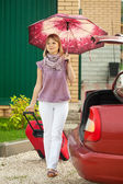 Woman with luggage go to car — Stock Photo