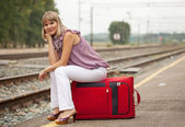 Woman with luggage waiting train — Stockfoto
