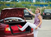 Woman packing her baggage into the car — Stock Photo