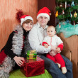 Family at home with Christmas tree — Stock Photo