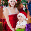 Foto Stock: Little boy and mother in Santa hat