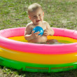 Happy baby swimming in inflatable pool — Stock Photo #6875490