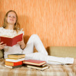 Female student with books on sofa - Stock Photo