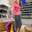 Woman with shopping bags at shoes shop — Stock Photo