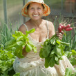 Smiling woman picking radish — Stock Photo