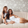 Smiling women sitting in livingroom — Stock Photo