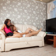 Women lying with TV Remote control — Stock Photo #6875718
