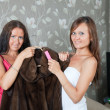 Stock Photo: Two women cleaning fur coat