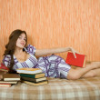 Stock Photo: Girl lying on sofwith books