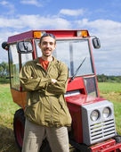 Farmer with tractor on meadow — Stock Photo