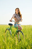 Girl riding bicycle in grass — Stock Photo