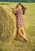 Girl on fresh straw — Stock Photo