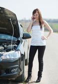 Woman calling by mobile near broken car — Stock Photo