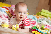 Baby girl with baby's clothes — Stock Photo