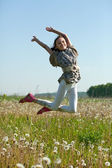 Teenager girl jumps at meadow — Stock Photo