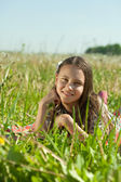 Teen girl lying in meadow grass — Stock Photo