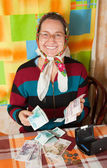 Happy senior woman with money — Stockfoto