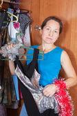 Mature woman thinking at wardrobe — Stock Photo