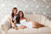 Lächelnd frauen sitzen im wohnzimmer — Stockfoto