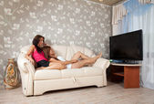 Women lying with TV Remote control — Stock Photo