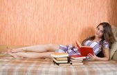 在沙发上的女孩阅读书 — 图库照片