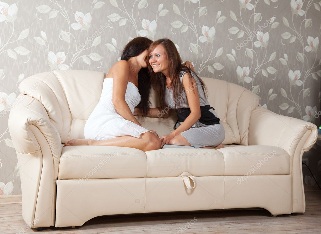 Two gossips women sitting on sofa in home  Stock Photo #6875704