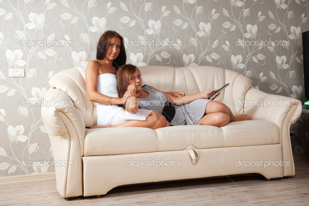 Two mid adult women look cinema laying on sofa  Stock Photo #6875705