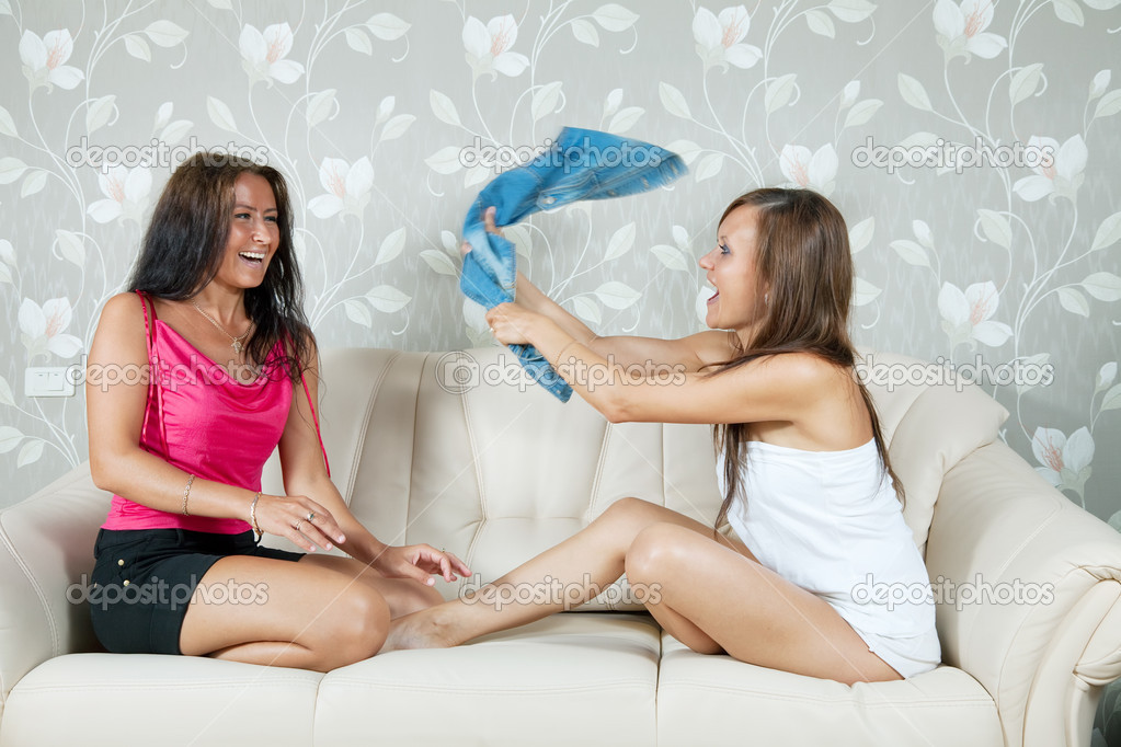 Happy girls playing with clothes on sofa in livingroom at home  Stock Photo #6875726