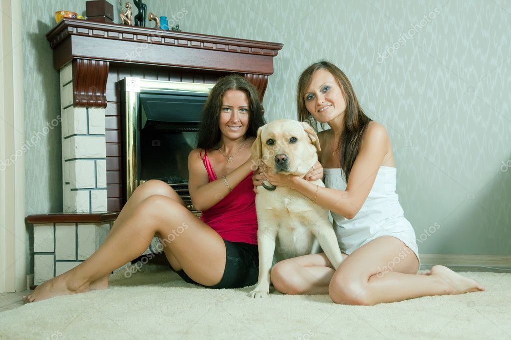 Two mid adult women with  labrador retriever in home interior  Stock Photo #6875760
