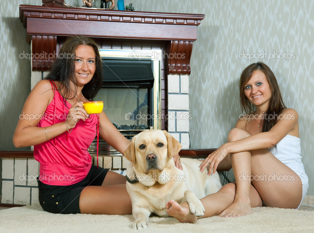Two mid adult women with  labrador retriever in home interior. Focus on  left woman only — Stock Photo #6875762
