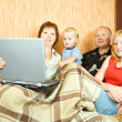 Stock Photo: Family on sofa with laptop