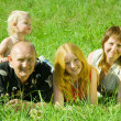 Family of four laying on grass — Stock Photo