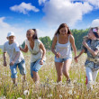 Four friends running at meadow — Stock Photo