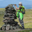 Stock Photo: Alpinist wommaking stone heap