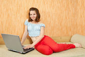 Girl with laptop on sofa — ストック写真